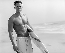 muscular surfer holding a surfboard by the ocean in Montauk, NY