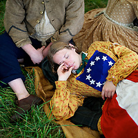 Wearing the 1st National Confederate Flag on her dress, Adrienne Robertson, from Richmond, VA, slumbers during a downpour at the 150th Antietam Civil War Reenactment in Boonsboro, Maryland.