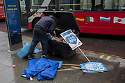 As a tour bus drives past, a rough-looking man searches through a bin, on 8th March 2017, London borough of Westminster, England.