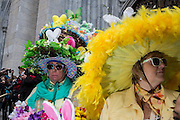 New York, NY, USA-27 March 2016. A woman wears a very large brimmed hat, bordered by yellow feathers, and a man with a multi-tierd hat with Easter baskets, on the steps of St. Patrick's Cathedral at the annual Easter Bonnet Parade and Festival.