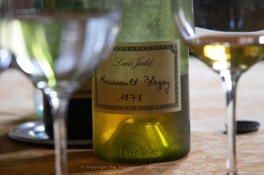 A half empty dusty old bottle with a hand written label saying Louis Jadot Meursault Blagny 1978 white burgundy and two glasses of wine on a dining table backlit backlight, Maison Louis Jadot, Beaune Côte Cote d Or Bourgogne Burgundy Burgundian France French Europe European