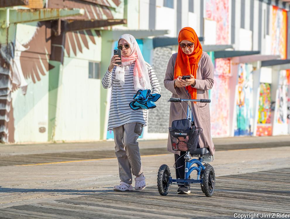 Two Muslim women catch up on social media as they stroll along the boardwalk.