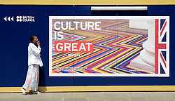 © Licensed to London News Pictures. 30/05/2012. London, UK A woman smokes a cigarette outside the office of The British Council near a poster saying 'Culture is Great Britain' Preparations today 20th May 2012 around London ahead of The Queen's Diamond Jubilee this weekend. Photo credit : Stephen Simpson/LNP
