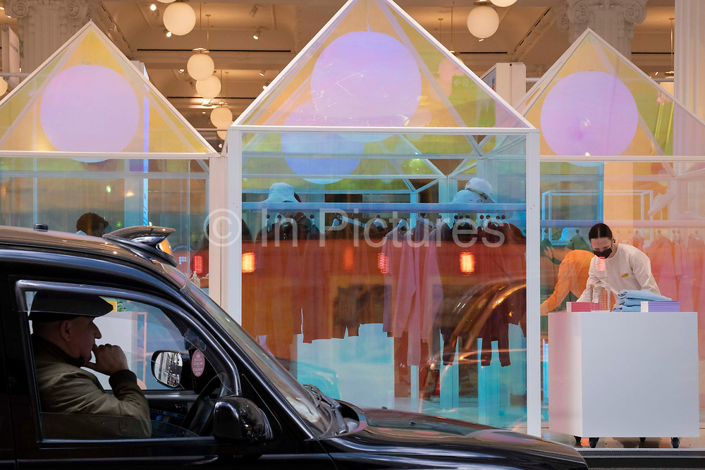 On the day that the UK government eased Covid restrictions to allow non-essential businesses such as shops, pubs, bars, gyms and hairdressers to re-open, a black cab driver waits for the next fare outside Selfridges, on 12th April 2021, in London, England.