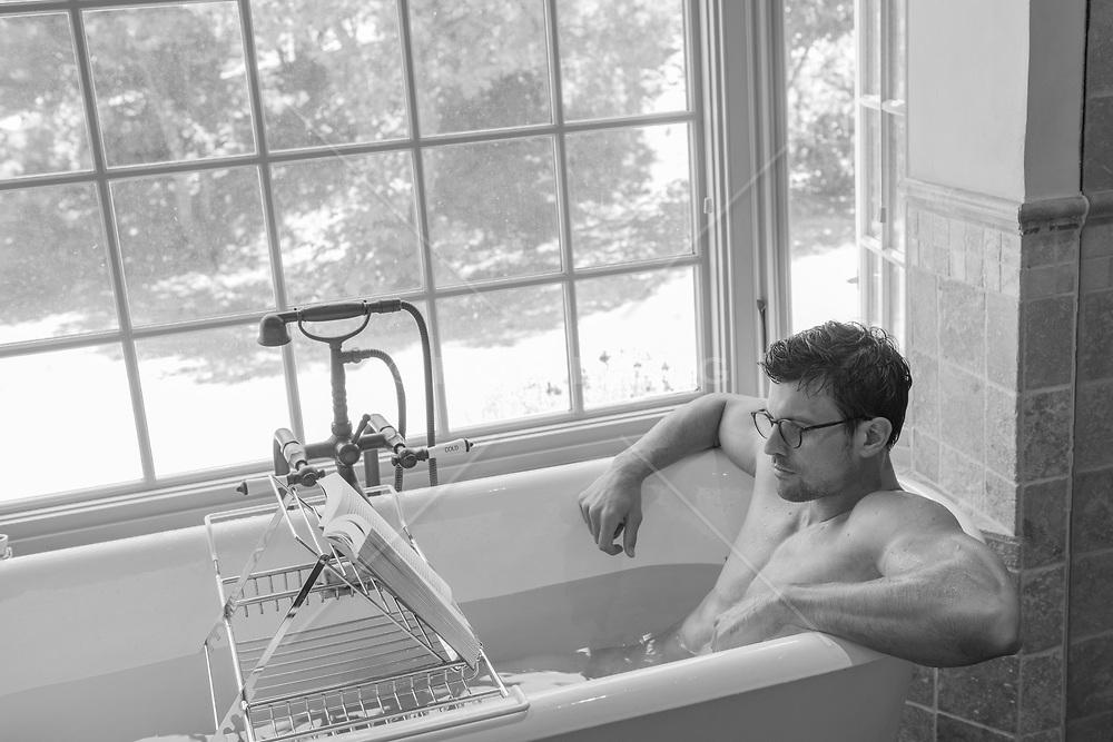hot guy in a bathtub reading a book