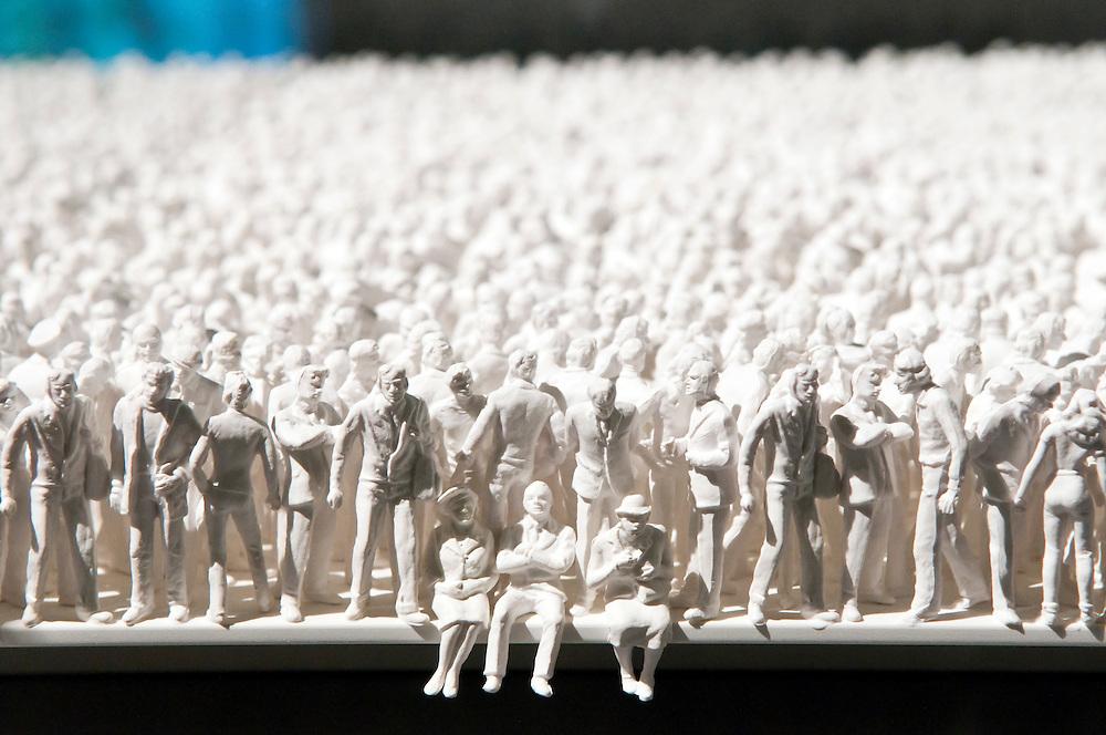 Ein Tisch randvoll mit menschlichen Figuren soll die zunehmende Erdbevölkerung veranschaulichen             |table covered with human figures, symbolic image over population