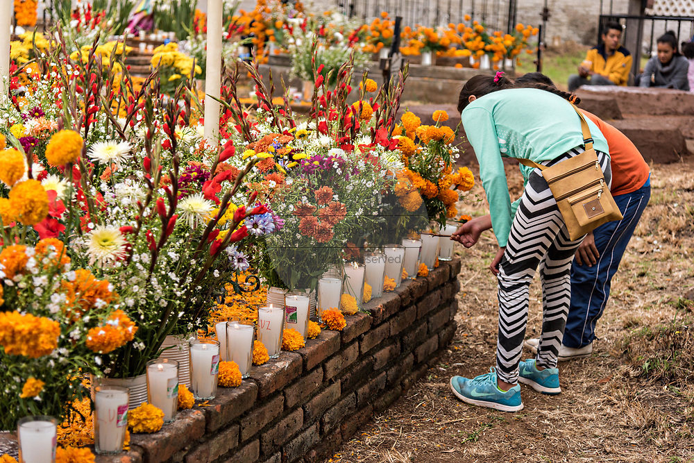 Children light candles along a gravesite decorated with marigolds and flowers for the Day of the Dead festival October 31, 2017 in Tzintzuntzan, Michoacan, Mexico.