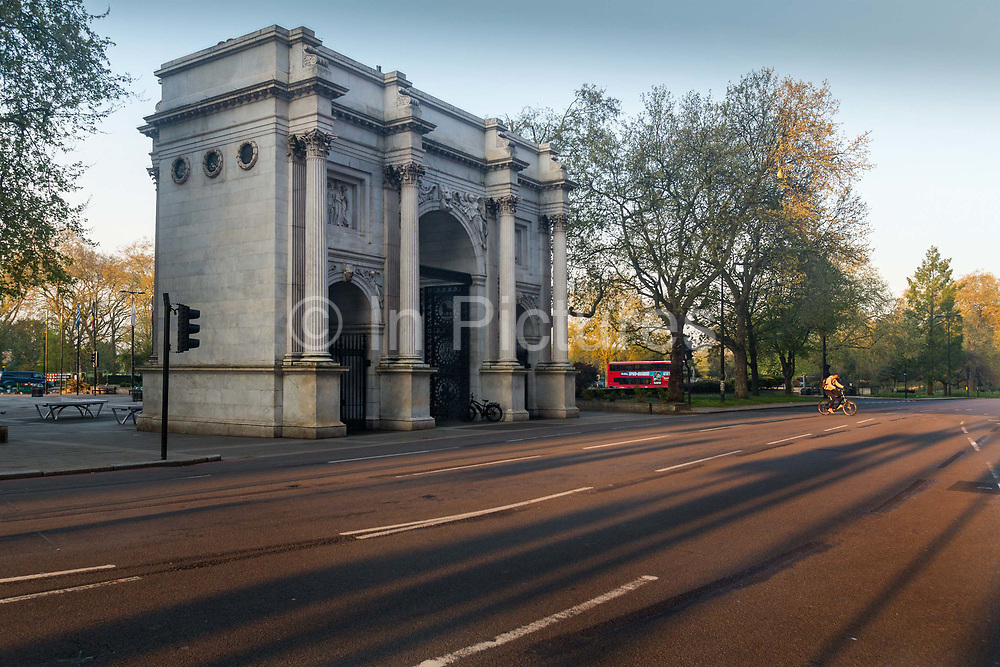 Marble Arch during 8am rush hour, on 16th April 2020 in London, United Kingdom. Normally crowded with people, London is like a ghost town as workers stay home under lockdown during the Coronavirus pandemic. Marble Arch is a 19th-century white marble-faced triumphal arch in London, England. The structure, based on that of the Arch of Constantine in Rome, was designed by John Nash in 1827 to be the state entrance to the cour dhonneur of Buckingham Palace. In 1851, on the initiative of architect and urban planner Decimus Burton, a one-time pupil of John Nash, it was relocated and following the widening of Park Lane in the early 1960s to where it is now sited, incongruently isolated, on a large traffic island at the junction of Oxford Street, Park Lane and Edgware Road.