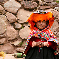 Americas, South America; Peru, Cusco. A young Peruvian girl learns the family trade of weaving at Awana Kancha.
