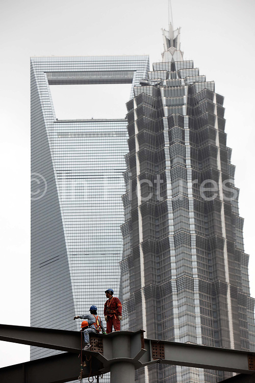 Construction workers rest on a steel beam in front of two landmarks in Shanghai, China on 29 September 2009.  The taller building on the left is the World Financial Center while the one on the right is the Jinmao Tower.