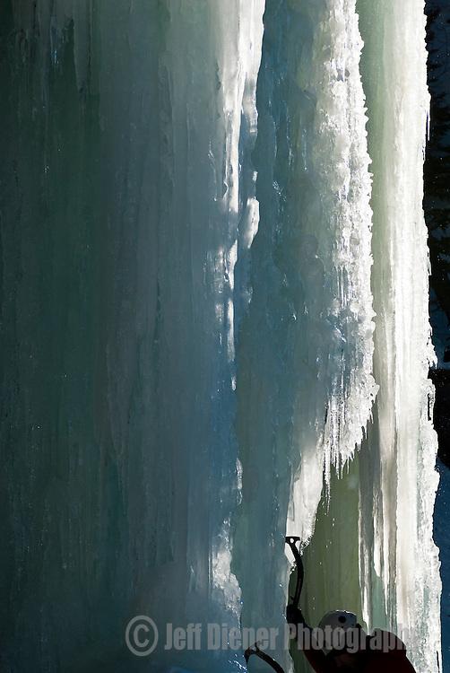 A young man climbs ice in Hyalite Canyon near Bozeman, Montana.