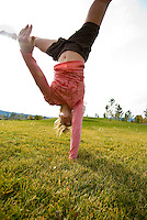 A young woman does a handstand at the park in Victor, Idaho.