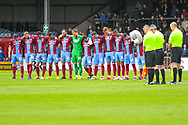 Scunthorpe United players observe a minute silence during the EFL Sky Bet League 1 match between Scunthorpe United and Bradford City at Glanford Park, Scunthorpe, England on 27 April 2019.