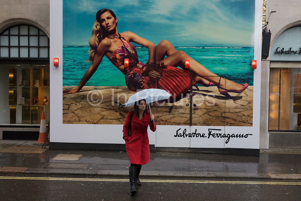 The fantasy of a model sunbathing on a beach is the opposite the experience of a local girl on a dark and rainy London on an April morning. The difference between dream and dystopia are evident in this backdrop, an ad for Salvatore Ferragamo (1898 – 1960) who was an Italian shoe designer. He worked with many Hollywood stars in the 1920s, before returning to Italy to found the eponymous company making unique hand-made footwear. Film stars and celebrities continue to patronize his company, which has evolved into a luxury goods empire spanning the world.