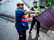 23 AUGUST 2017 - BANGKOK, THAILAND: A Bangkok city workers throw a basket of trash from Pom Mahakan into a truck. Bangkok city officials this week started cleaning up the area around cremation site for Bhumibol Adulyadej, the Late King of Thailand. Work started by cleaning Pom Mahakan, a historic fort about two kilometers northeast of the cremation site. They are going to scrub and paint the fort's historic exterior walls, which were built in the late 18th century. The King, who died on 13 October 2016, will be cremated on 26 October 2017.      PHOTO BY JACK KURTZ