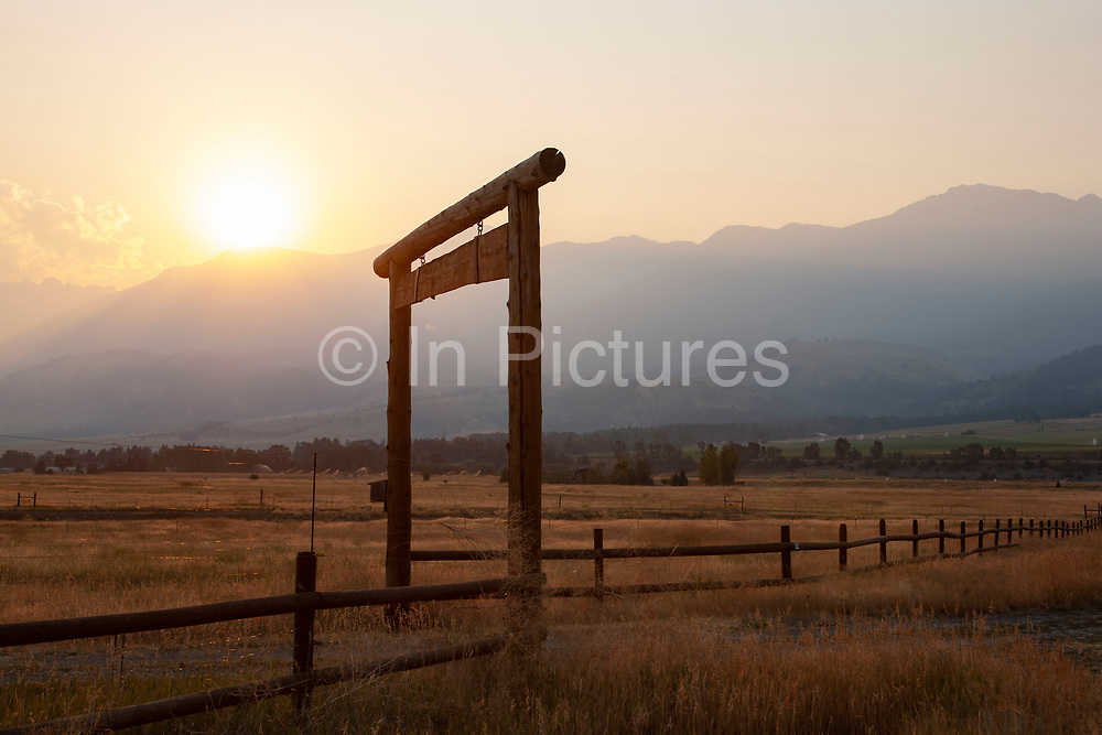 Sun streams over the edge and casts a shadow down the mountainside of Mount Cowen at sunrise. Dawn in Paradise Valley, near Livingstone, Montana can be a spectacular event as the valley floor lights up a fresh day. Grassland comes to life and ranches start working.