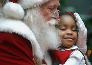 23 DEC 02 (KPSANTA)  by Karen Pulfer Focht: Affiong Enyenihi of Collierville, delights in a hug from Santa on Monday at Wolfchase Galleria .  It was the two-year-olds first ever visit with Santa and one she will remember.