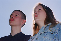 Teenage girl and boy looking into the distance,