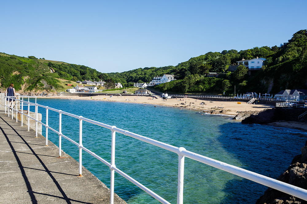 View from the pier over the sea and towards the beach at Greve de L'Ecq on a sunny day in Jersey, Channel Islands