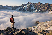 Ethan Welty looks out towards Mount Fury and the rugged Northern Picket Range from camp below Mount Challenger, North Cascades National Park, Washington.
