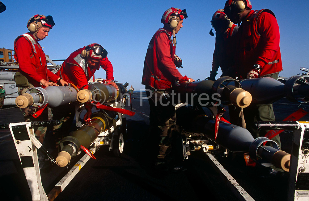 Red shirted ordnance men prepare to fit smart bombs and missiles to an F/A-18 fighter jet on deck of USS Harry S Truman. Launched on 7 September 1996 and costing US$4.5 billion, the Truman (CVN-75) is the eighth Nimitz-class supercarrier of the United States Navy, named after the 33rd President of the United States, Harry S. Truman. The Truman is the largest of the US Navy's fleet of new generation carriers, a 97,000 ton floating city with a crew of 5,137, 650 are women.