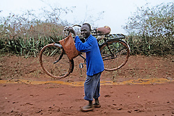 Man Carrying Bicycle In Mud