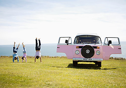 Man and Two Children Doing Handstand by Camper Van