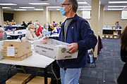 02 NOVEMBER 2020 - DES MOINES, IOWA: Election workers distribute mail in ballots to be opened at the Polk County Auditor's Office in Des Moines Monday. Officials started opening mail in ballots Monday morning but won't start counting ballots until Tuesday morning. This is the last day of early voting before the 2020 US presidential election. The line to vote at the Polk County Auditor's Office was 4 blocks long Monday morning. An elections official said that by November 3, which is Election Day, about 45 percent of the registered voters in Polk County will have already voted.     PHOTO BY JACK KURTZ
