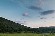 Cornwall, New York - The moon, at upper left, shines over fields and forests by Schunnemunk Mountain at twilight  on July 24, 2015.