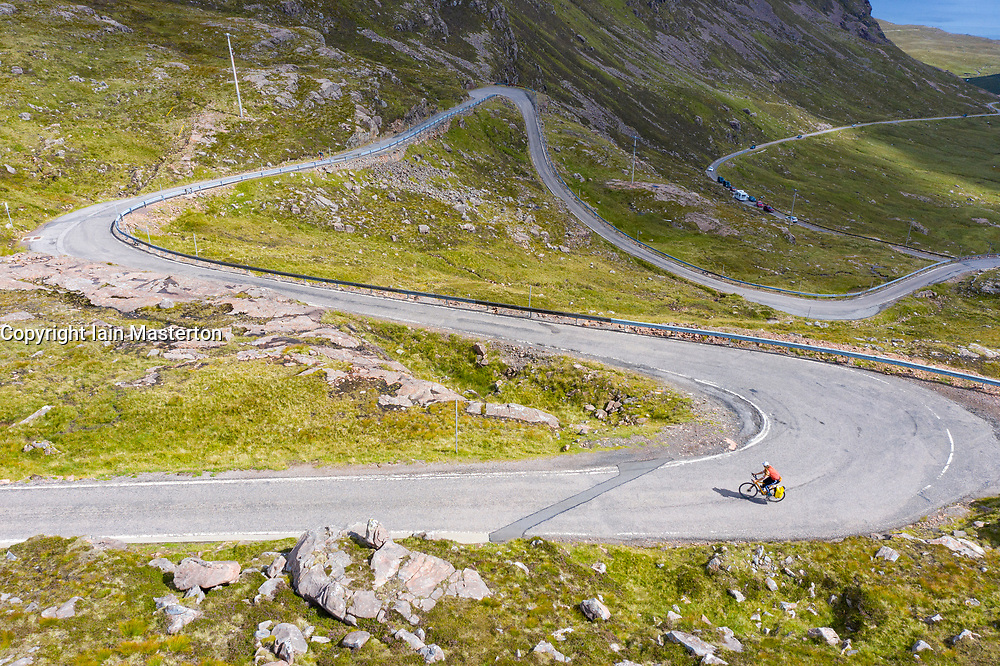 Cyclist climbing Bealach na Ba pass on Applecross Peninsula in Wester Ross Scotland, UK