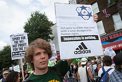 © licensed to London News Pictures. London, UK 28/07/2012. A protester posing with a placard against Adidas as anti-Olympics protesters marching from Mile End Park to Victoria Park in order to protest against the greed of the Olympic sponsors. Photo credit: Tolga Akmen/LNP