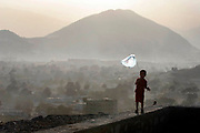 A boy flies a kite made of a plastic bag on the Bibi Mahro Hill in Wazir Akbar Khan section of Kabul as the sun sets behind the mountain on one October afternoon in 2006. Kite-flying, an traditional sport popular in central and east Asia, was one of the 'un-islamic' sports which the Taliban had banned during its repressive rule between 1996 and 2001.