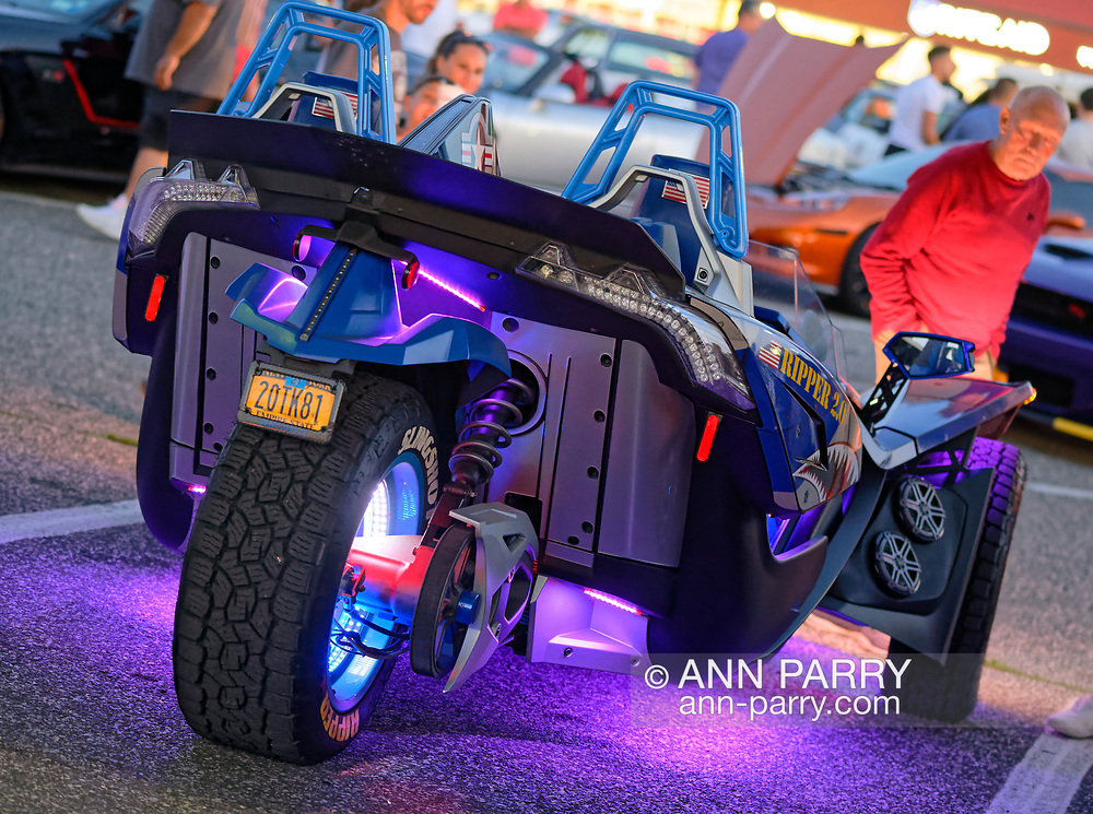 Bellmore, New York, U.S. July 30, 2021. A Polaris Slingshot, a three-wheel autocar, is colorfully lit at the Bellmore Friday Night Car Show, held at the Bellmore Long Island Rail Road parking lot. Event has hundreds of visitors enjoying classic and customized cars and pleasant summer weather. The Chamber of Commerce of the Bellmores hosts the cruise nights each Friday from May 14 to October 1, 2021, weather permitting.