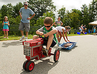Caleb Jackson has to add a bit more steam when Kelley Allen puts a couple more bricks onto his load during the children's pedal tractor pull event at Belmont Old Home Day festivities Saturday morning.  (Karen Bobotas/for the Laconia Daily Sun)