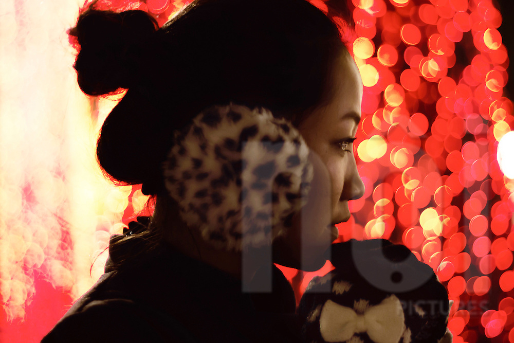 Bokeh red lights shine behind a young Vietnamese woman wearing earmuffs on a cold evening in Hanoi, Vietnam, Southeast Asia