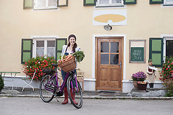 Portrait of a mid adult woman with bicycle and vegetables standing on street in front of wholefood shop, Bavaria, Germany