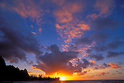 Pink clouds and silhouetted peaks at sunset over Tunnels Beach, Na Pali Coast, Island of Kauai, Hawaii