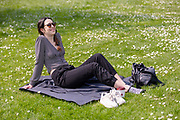 A woman wearing sunglasses relaxes on a blanket on the grass during sunny spring weather at lunch time in Regents Park in London, England on April 17, 2019.