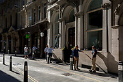 With the UK death toll reaching 34,813, with a further 541 victims in the last 24hrs, the government's pandemic lockdown has eased to another stage and drinkers keep their social distances while enjoying pints from an unusually open pub in the City of London, the capital's financial district, on 1st June 2020, in London, England.