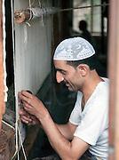 A carpet weaver working in Srinigar, Kashmir, India