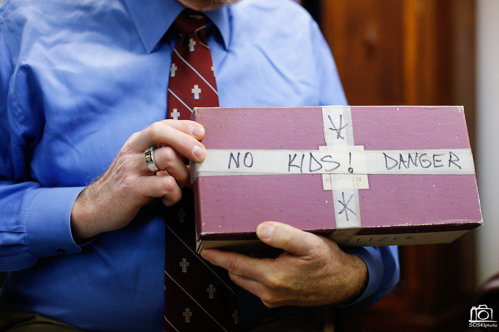 """Rev. Bruce Buchanan holds a shoebox with the label """"No Kids! Danger,"""" during a gun buy-back in The Stewpot parking garage in Dallas, Texas, on January 19, 2013.  The shoebox was turned in with a handgun during a previous First Presbyterian Church of Dallas gun buy-back.  (Stan Olszewski/The Dallas Morning News)"""