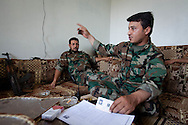 Two soldiers from the Free Syrian Army discuss disarming the country after the conflict is over, keeping detailed lists of who owns which weapons, and who has ammunition. Kureen, Idlib, Syria. 17/06/2012