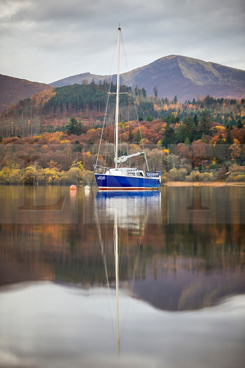 © Licensed to London News Pictures. 06/11/2019. Keswick UK. A boat & the surrounding mountains reflect in to the still water of Derwentwater lake in Keswick at first light this morning in Cumbria. Photo credit: Andrew McCaren/LNP