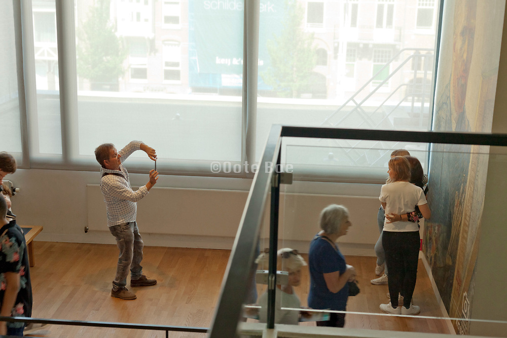 tourists making photo's with a large painting poster at the Van Gogh Museum
