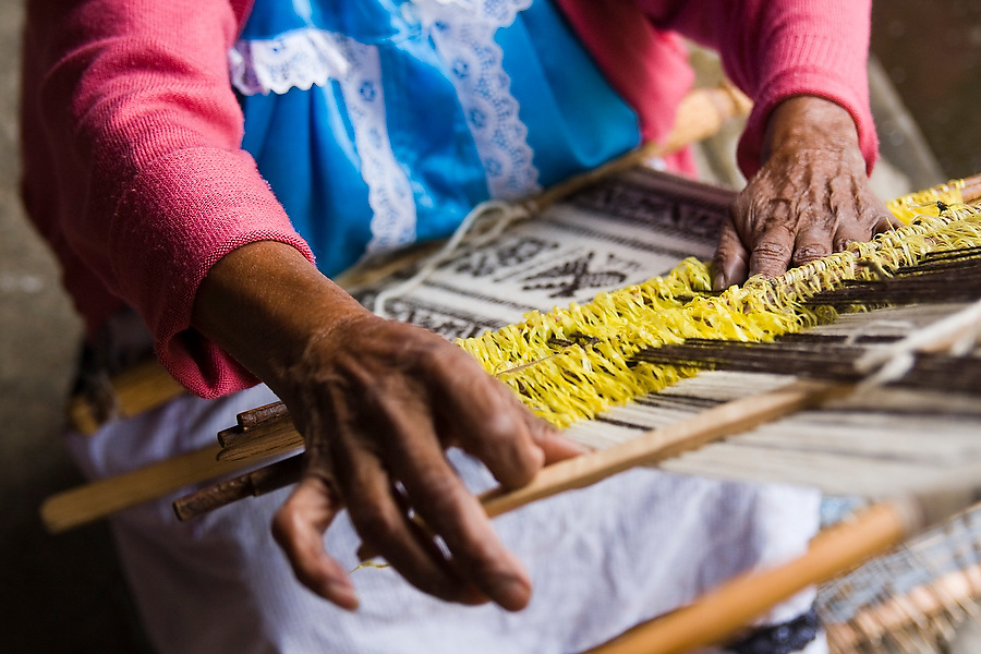 An elderly Purepecha woman weaves a shawl on a small loom in Paracho, Michoacan state, Mexico on August 7, 2008 at the artisan market held during the annual Feria Internacional de la Guitarra.