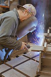 Man welding at engineering works wearing protective visor,