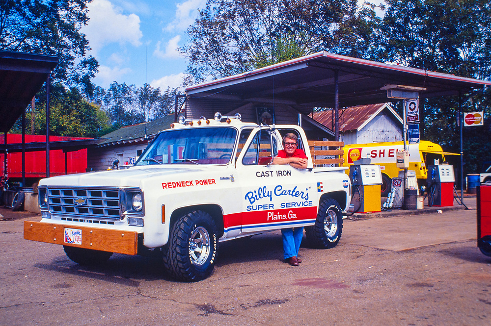 """Billy Carter with his new """"Redneck Power"""" pickup truck at his Plains, Georgia gas station. A nodel of the pickup was produced by Revell and sold internationally.  William Alton - Billy - Carter (March 29, 1937 – September 25, 1988) was an American farmer, businessman, brewer, and politician, and the younger brother of U.S. President Jimmy Carter. Carter promoted Billy Beer and was a candidate for mayor of Plains, Georgia. Carter was born in Plains, Georgia, to James Earl Carter Sr. and Lillian Gordy Carter. He was named after his paternal grandfather and great-grandfather, William Carter Sr. and William Archibald Carter Jr. respectively. He attended Emory University in Atlanta but did not complete a degree. He served four years in the United States Marine Corps, then returned to Plains to work with his brother in the family business of growing peanuts. In 1955, at the age of 18, he married Sybil Spires (b. 1939), also of Plains. They were the parents of six children: Kim, Jana, William """"Buddy"""" Carter IV, Marle, Mandy, and Earl, who was 12 years old when his father died."""