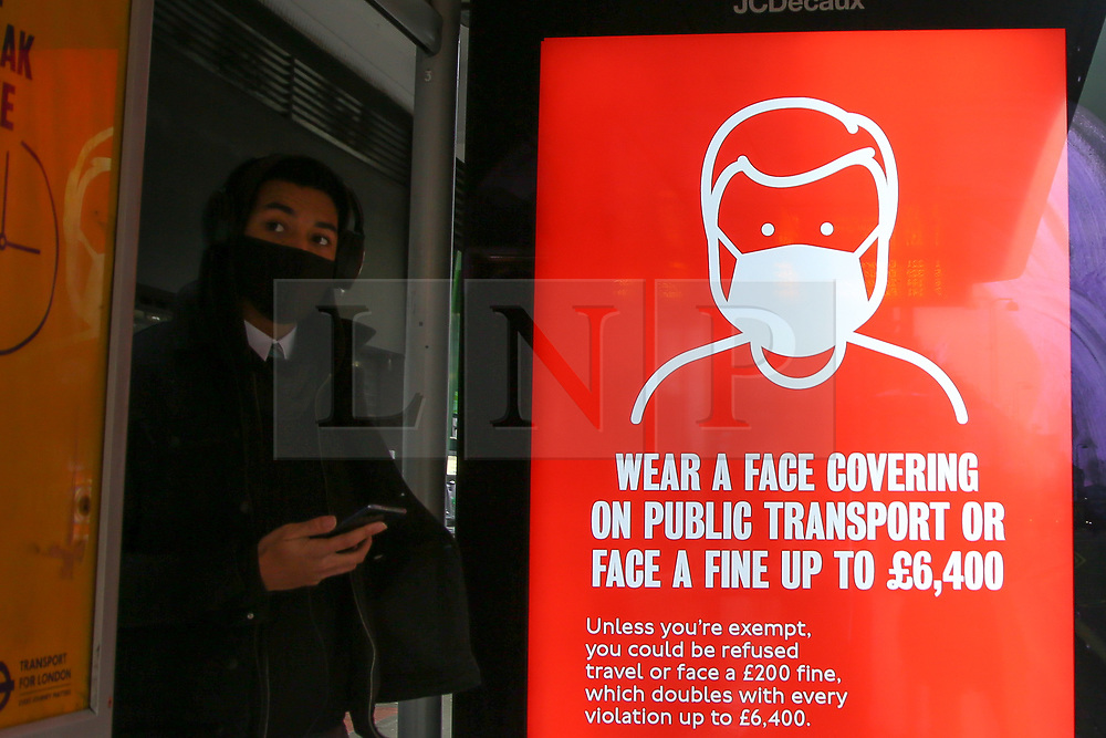 © Licensed to London News Pictures. 07/01/2021. London, UK. A commuter wearing a protective face covering stands next to the Transport for London's 'Wear a face covering on public transport to protect each other' campaign poster at a bus stop in north London. Police have powers to fine people who are not wearing a coverings when travelling on public transport, including London buses. Lockdown measures are now in force across the UK, after Prime Minster Boris Johnson announced the new restrictions earlier this week asked everyone to 'stay at home' and only leave for the specific reasons, until mid-February. Photo credit: Dinendra Haria/LNP