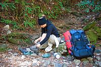Backpacker reorganizes on Pine Ridge Trail, Big Sur, California.