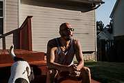 """BIRMINGHAM, AL – SEPTEMBER 4, 2020: Jonathan Perez, 31, sits outside with his dog Meat Mountain.<br /> <br /> As the coronavirus pandemic continues to grow in the United States, the cost of recovery from Covid-19 has varied considerably for Americans. Jonathan Perez, 31, contracted Covid-19 and was admitted to a nearby hospital in Birmingham, where his condition quickly worsened. """"They didn't think I'd make it,"""" Perez said. """"I'd said my peace."""" Fortunately Perez recovered, but he'd incurred medical bills in excess of $50,000. The uninsured Marine veteran was told his entire bill would be covered by the hospital using funds from the CARES Act. In the end, he ended up paying around $800. Perez, who has been virus-free for about a month, still suffers from fatigue. He spends his time trying to recover full use of his lungs by walking his dogs several times a day. """"I'm just thankful to be here,"""" he told me."""